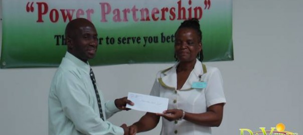 Acting General Manager of DOMLEC Dave Stamp presenting member of the board of directors of the Education Trust Fund Glenda Castle with the EC$10,000 donation